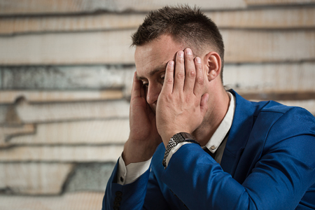 overworking: Tired business man at workplace in office holding his head on hands. Sleepy worker early in the morning after late night work. Overworking, making mistake, stress, termination or depression concept Stock Photo