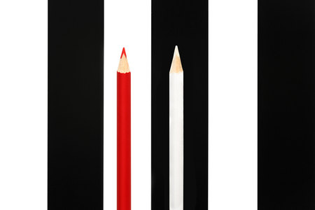 dissent: Red pencil standing out from crowd of black and white fellows on bw stripe background. business success concept of leadership an uniqueness,independence, initiative,strategy, dissent, think different