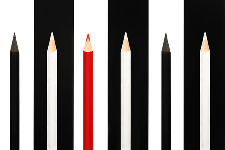 dissent: Red pencil standing out from crowd of black and white fellows on bw stripe background. business success concept of leadership uniqueness, independence, initiative, strategy, dissent, think different