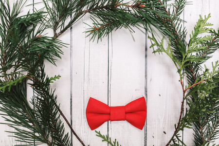 christamas: Christmas decoration in vintage toning on white wooden background with red bowtie and fir branch. Xmas decorative ornaments for design. Art work with texture for holiday new year 2017