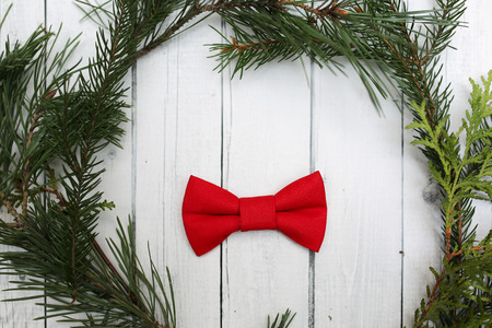 christamas: Christmas decoration in vintage toning on white wooden background with red bowtie and fir branch. Xmas decorative ornaments for degign. Art work with texture for holiday new year 2017