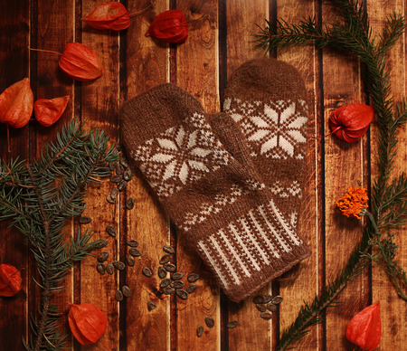 winter cherry: Brown warm Mittens on vintage wooden texture. Christmas and New Year background concept. spruce branches, orange winter cherry
