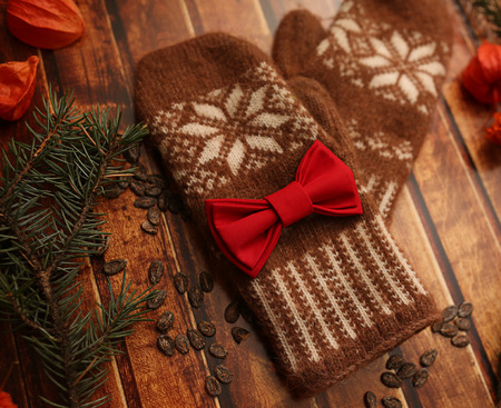 winter cherry: Brown warm Mittens on vintage wooden texture. Christmas and New Year background concept. spruce branches, orange winter cherry and red bowtie Stock Photo
