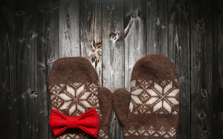 winter cherry: Brown warm Mittens on vintage wooden black table texture. Christmas and New Year background concept. spruce branches, orange winter cherry and red bowtie Stock Photo