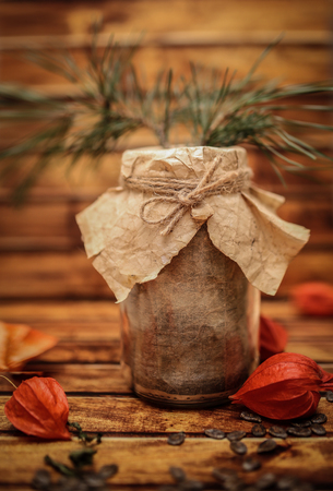 winter cherry: Empty bank in vintage style for blurry wooden background. Design work.Autumn winter Food still-life composition with winter cherry and retro pot or jar with craft paper and designer gift wrap package. Stock Photo