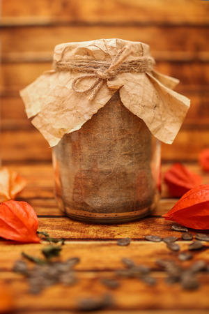 Empty bank in vintage style for blurry wooden background. Design work.Autumn winter Food still-life composition with winter cherry and retro pot or jar with craft paper and designer gift wrap package. Stock Photo
