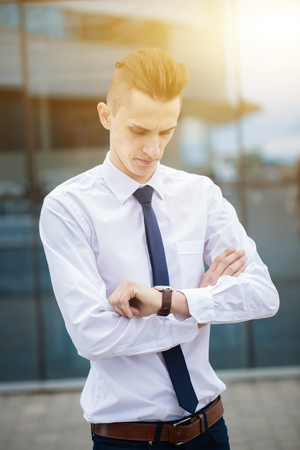 smart businessman manager looking at watch, watch the time. business concept. blue blur citypoint background Stock Photo