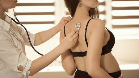 Friendly female medicine doctor holding stethoscope and listening to pregnant woman standing for encouragement, empathy, cheering,support, medical examination. New life of abortion concept. Stock Photo