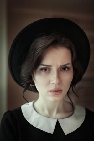 ifestyle: Close up fashion ifestyle portrait of beautiful girl in black in sunlight near the window. Modern split toning.