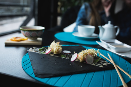 Tiger shrimps in Chinese noodles with sauce on black plate. Asian food concept. People on background in restaraunt place with wooden table. copy space for text, design Stock Photo