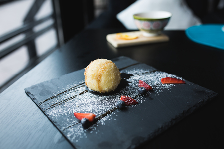 Grilled ice-cream in coconut with sauce on black stone plate. Asian food background. Eating concept. Restaraunt place with wooden table. Copy space for text, design.