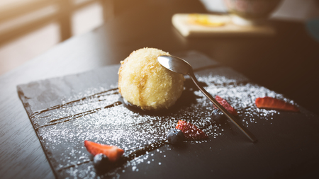 Grilled ice-cream in coconut with sauce and fruits on black stone plate with tea spoon. Asian food background. Eating concept. Restaraunt place with wooden table. Flare Copy space for text, design Stock Photo