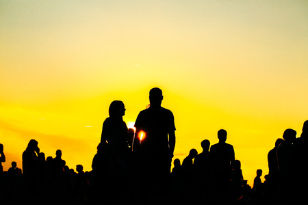 crowd happy people: Silhouette of people in sunset on holiday. summer lifestyle. Colorful warm yellow toning. Recreation in park nature. Music Festival on outdoor.