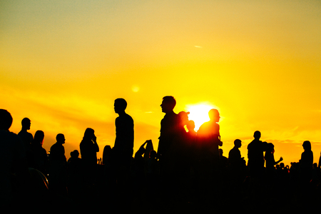 silhoutte: Silhouette of people in sunset on holiday. summer lifestyle. Colorful warm yellow toning. Recreation in park nature. Music Festival on outdoor.