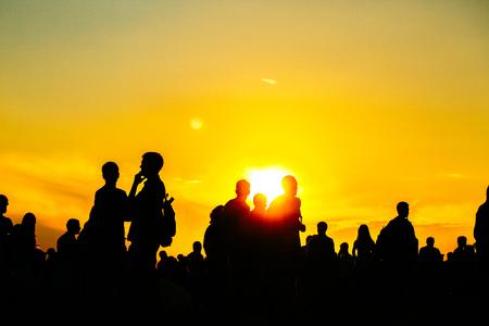 Silueta de personas en la puesta de sol en vacaciones. estilo de vida de verano. Tonalidad amarilla caliente colorida. Recreación en la naturaleza del parque. Festival de música en exterior.