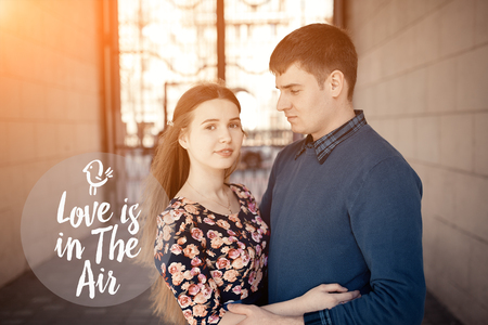 farewell party: Love is in the air text frame. Pair in love in the city walking, laughing, kissing and have fun. Colorful warm yellow toning. Stock Photo