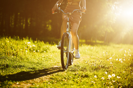 Funny girl driving bicycle outdoor. Sunny summer lifestyle concept. Woman in dress and hat in Field with dandelions. Female ride in park. Light photo effect for text. Copyspace for design Stock Photo
