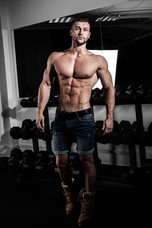 retouched: man in gym. Muscular bodybuilder guy doing exercises with barbell. Strong person. Sports background. Young athlete ready for weight lifting training.