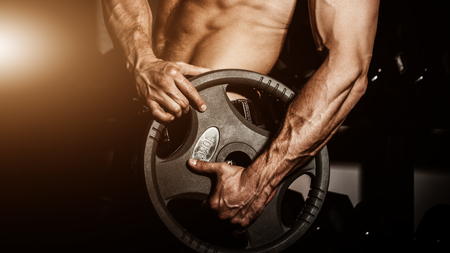 retouched: man in gym. Muscular bodybuilder guy doing exercises with barbell. Strong person with Tense strong male hand with veins barbell. Flare for text and design.