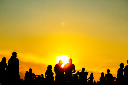 Silhouette of people in sunset on holiday. summer lifestyle. Colorful warm yellow toning. Recreation in park nature. Music Festival on outdoor.