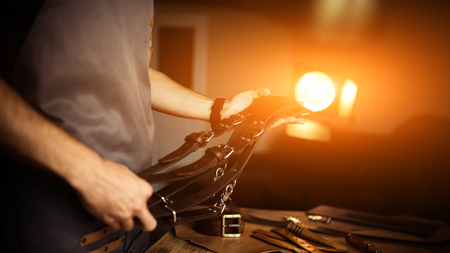 Working process of the leather craft in the workshop. Man holding photographers belt for camera.Wooden background. Tanner in old tannery.Close up arms.Warm Light for text and design. Web banner size.