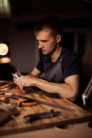 Working process of the leather belt in the leather workshop. Man holding crafting tool and working. Tanner in old tannery. Wooden table background. Close up man arm. Stock Photo