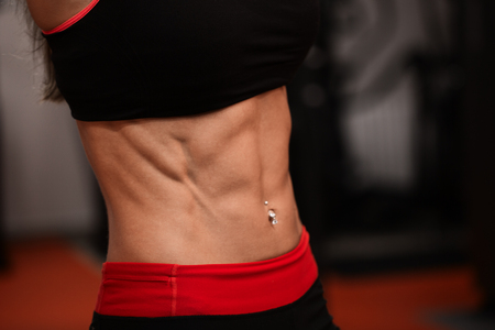 Sporty girl in gym show abs. woman in tonus.