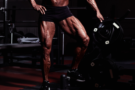 Sportsman in gym. Guy doing exercises. Closeup portrait of legs with veins. Male model with tanned skin. Sexy man bodybuilder standing with barbell Stock Photo