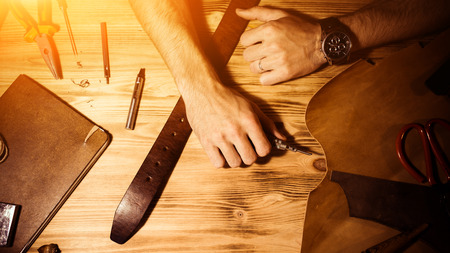 Working process of the leather belt in the leather workshop. Man holding hands on wooden table. Crafting tools on background. Tanner in old tannery. Warm Light for text and design. Web banner size. Stock Photo
