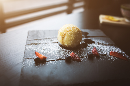Grilled ice-cream in coconut with sauce on black stone plate. Asian food background. Eating concept. Restaurant place with wooden table. Flare Copy space for text, design