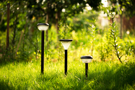 Plastic garden flashlight standing on the ground in the garden green grass. It is shining yellow light. Summer mood image. Stock Photo