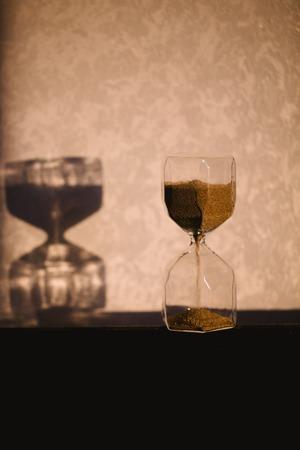 Hourglass with shadow on wall. Time passing concept for business deadline, urgency and running out of time. Sandglass, egg timer showing the last minute or time out. Copy space for text and design.