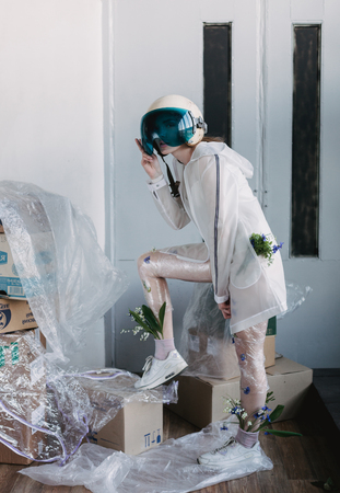 Fashion portrait of girl in plastic trend clothes with space helmet on head. Eco styling. Model standing in poses.