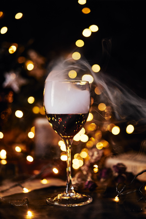 Festive atmosphere in the evening with a glass of red wine. Smoke creeping into clubs in glass and light bokeh background. Christmas, New Years or Saint Valentine holiday.Golden color and soft focus. 스톡 콘텐츠