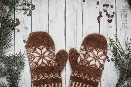 Brown mittens and spruce branches with snow on white wooden background. Holiday postcard design. Christmas and New Year concept.