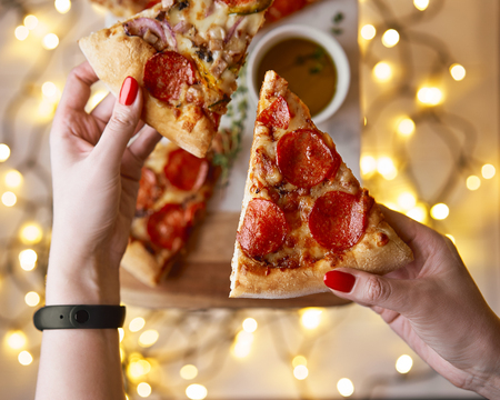 Christmas and New Year atmosphere. Womans hand takes slice of Italian pizza with melting tomato, pepperoni and cheese on a white marbel cutting board. Background with lights in bokeh and selective focus.