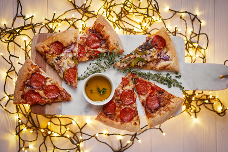Christmas and New Year atmosphere. Hot Italian pizza with melting tomato, pepperoni and cheese on a white marbel cutting board. Background with lights in bokeh. Foto de archivo