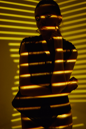 Beauty portrait of girl with light stripes and shadows in gold color. Hight quality retouching photo. Fashion glamour model.