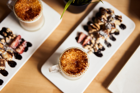 Two cups of Hot latte with baked caramel crust and sweet roll with banana and strawberry on the wooden table in coffe-shop. Coffee concept. Top view photo of two sets. Stock Photo