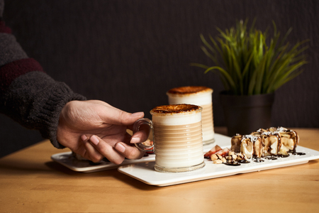 Mans hand hold cup of Hot latte with baked caramel crust and sweet roll with banana and strawberry on the wooden table in coffe-shop. Coffee concept.