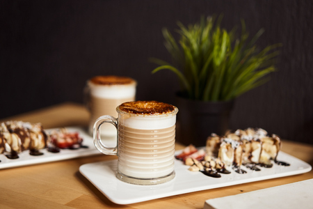 Two cups of Hot latte with baked caramel crust and sweet roll with banana and strawberry on the wooden table in coffe-shop. Coffee concept.