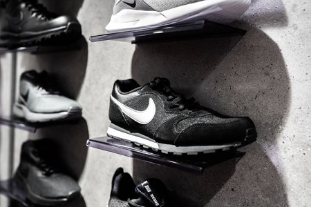 Nurmberg, GERMANY - February 27, 2019: The NIKE black sneakers on the shell in the shop. Fashionable foot wear shoes. Close up photo sport concept. Redakční
