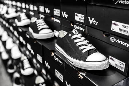 Nurmberg, GERMANY - February 27, 2019: The black sneakers on the shell in the shop. Fashionable foot wear shoes. Close up photo sport concept.