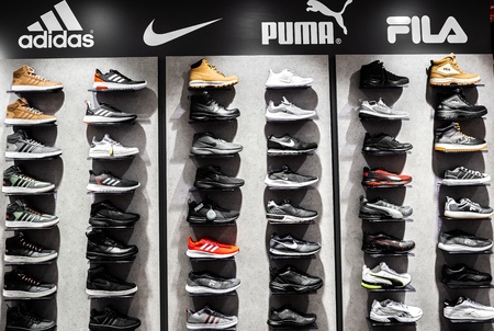 Nurmberg, GERMANY - February 27, 2019: The NIKE, ADIDAS, PUMA and FILA black sneakers on the shell in the shop. Fashionable foot wear shoes.
