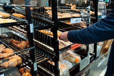 Fresh croissant on bread shelf in store. A man takes a fresh batch with a spatula. Food concept.