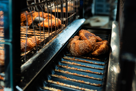Fresh croissant on bread shelf in store. Take a fresh batch with a spatula. Food concept.