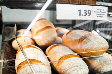 Fresh bread on shelf in store with price. Close up photo of food concept.