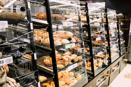Different fresh bread, croissants, brezels on shelf in store with price. Market time. Food photo concept of choice bread on breakfast. Stock Photo