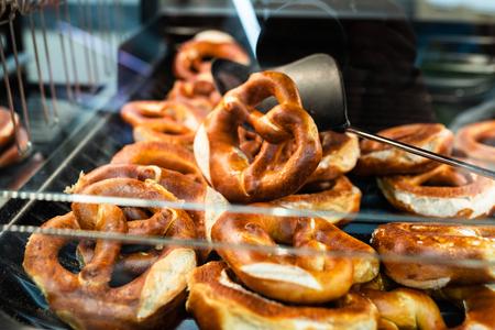 Germany national bakery - brezel. Close up Fresh pretzel on bread shelf in store. Take a fresh bavarian Brezel with a spatula. Breakfast food concept.