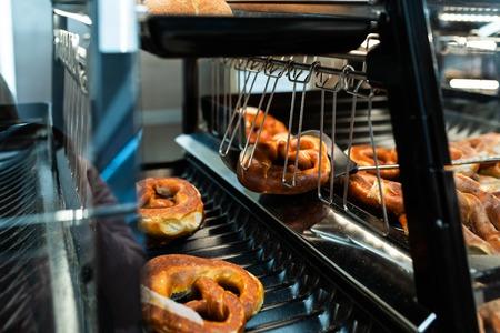 Germany national bakery - brezel. Fresh pretzel on bread shelf in store. Take a fresh bavarian Brezel with a spatula. Breakfast food concept. Stock Photo